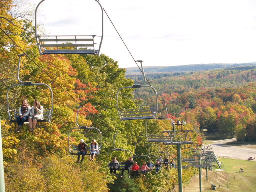 The chairlift at Treetops Resort is filled with people enjoying the fall colors.